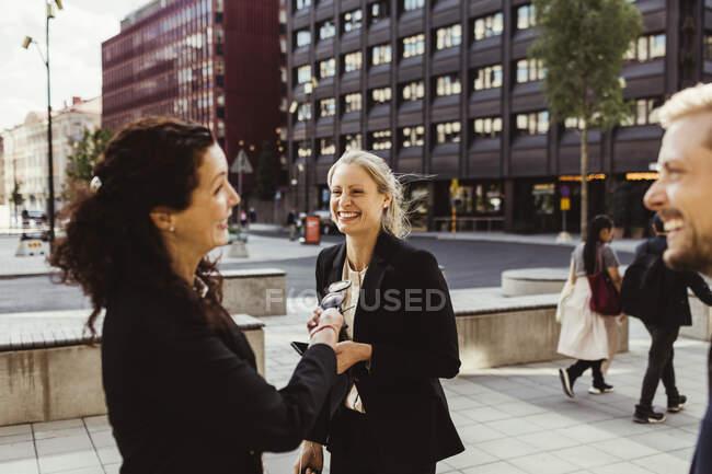 Empreendedora mulher sorrindo com colegas de trabalho ao ar livre — Fotografia de Stock
