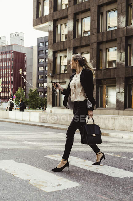 Female entrepreneur with smart phone crossing street — Stock Photo