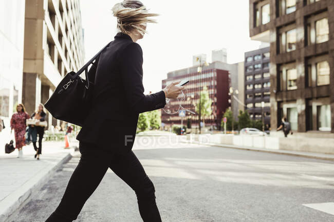 Businesswoman with smart phone crossing street — Stock Photo