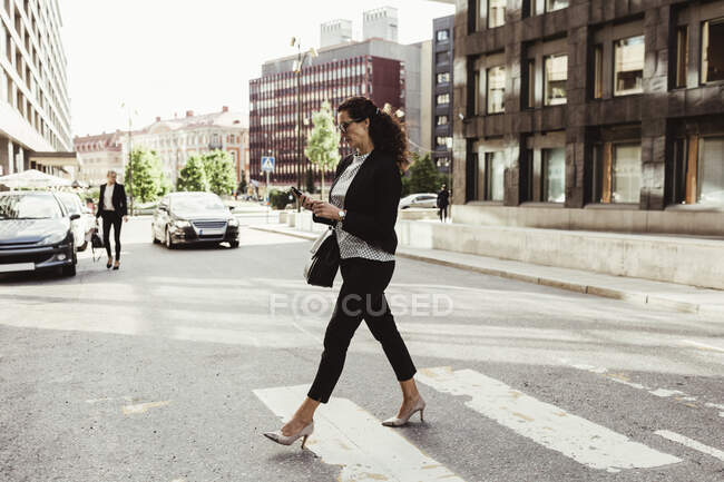 Businesswoman looking at smart phone while crossing street — Stock Photo