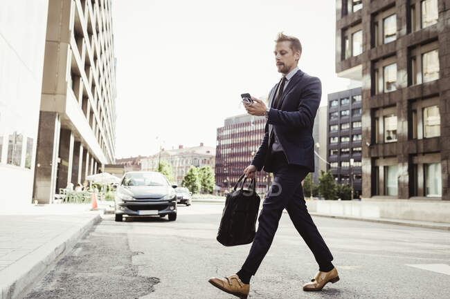 Male entrepreneur looking at phone while crossing street — Stock Photo