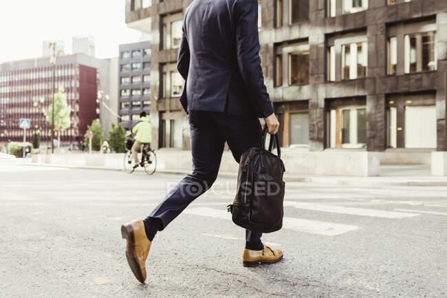 Bassa sezione di imprenditore maschile con borsa che attraversa strada — Foto stock
