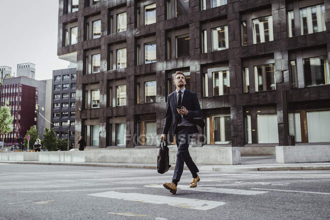 Male entrepreneur looking up while crossing street — Stock Photo
