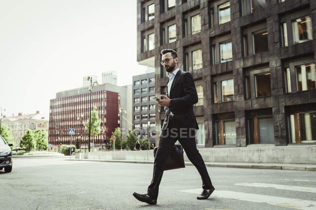 Affidabile uomo d'affari con borsa che attraversa la strada — Foto stock