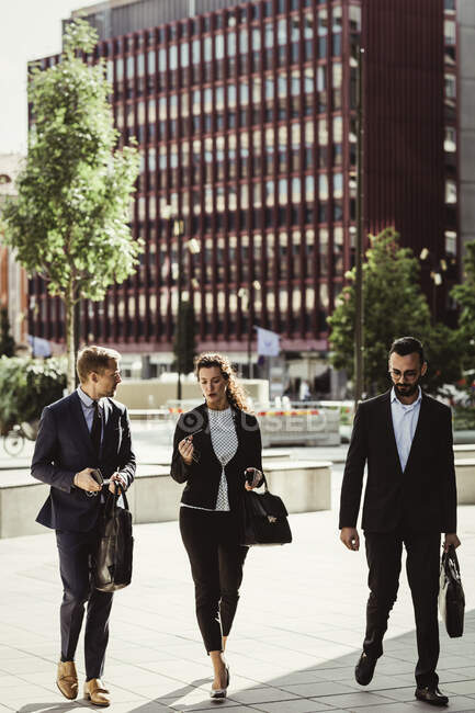 Entrepreneur discussing strategy with male and female colleagues while walking outdoors — Stock Photo