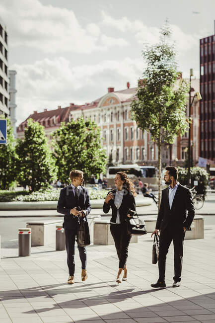 Female entrepreneur discussing strategy with male colleagues while walking outdoors — Stock Photo