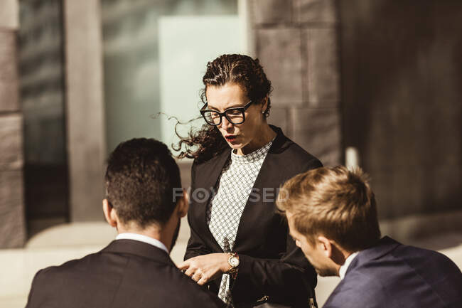 Female entrepreneur discussing business strategy with coworkers while standing outdoors — Stock Photo