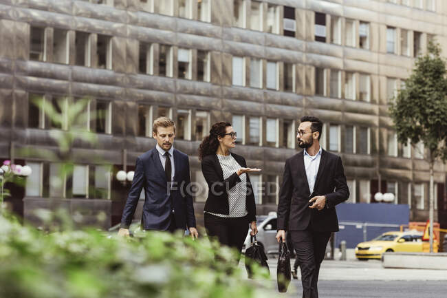 Female entrepreneur discussing business strategy with male colleagues while walking outdoors — Stock Photo