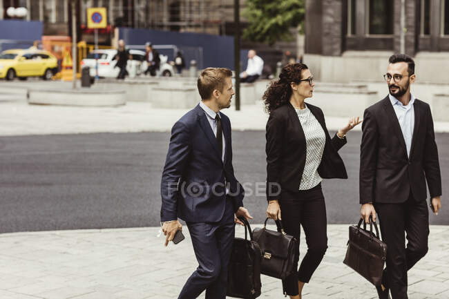 Female entrepreneur discussing business strategy with male coworkers while walking outdoors — Stock Photo