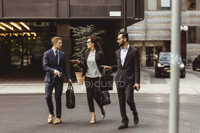Male and female entrepreneurs discussing business strategy while walking outdoors — Stock Photo