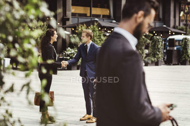 Male and female entrepreneurs shaking hands while standing outdoors — Stock Photo