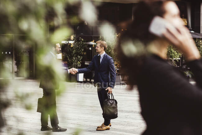 Male entrepreneurs shaking hands while standing outdoors — Stock Photo