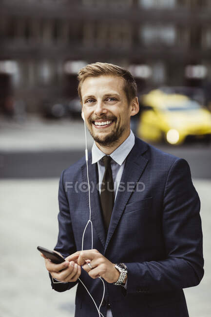 Portrait of smiling entrepreneur using smart phone through in-ear headphones while standing outdoors — Stock Photo