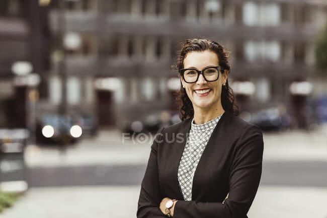 Portrait de femme d'affaires souriante avec les bras croisés debout à l'extérieur — Photo de stock