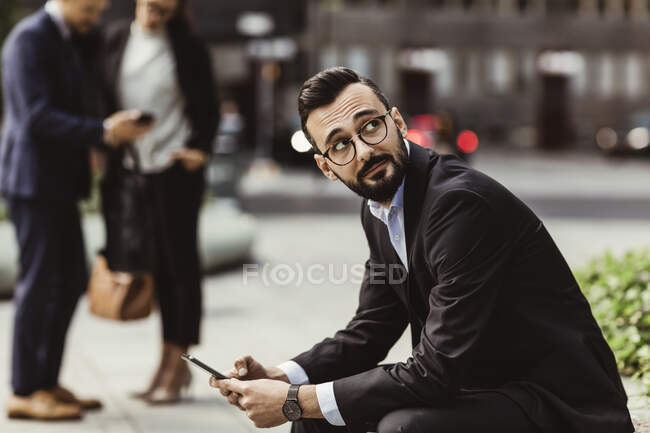 Businessman looking up while using mobile phone outdoors — Stock Photo