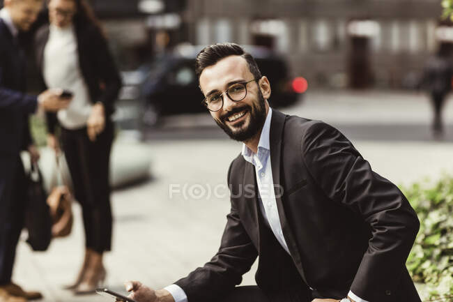Portrait of smiling businessman with mobile phone sitting outdoors — Stock Photo
