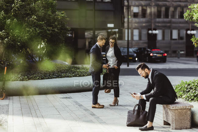 Businessman showing smart phone to female colleague while male coworker surfing net outdoors — Stock Photo