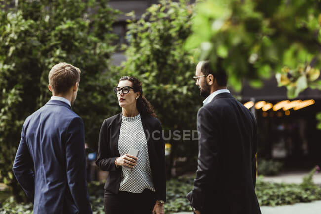 Female and male entrepreneurs discussing business strategy while standing outdoors — Stock Photo