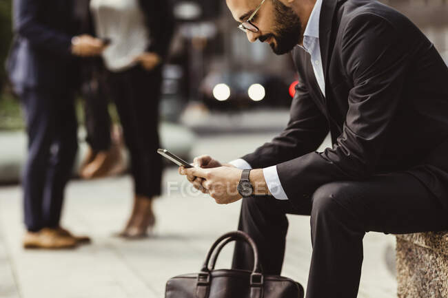 Businessman using smart phone while sitting on seat outdoors — Stock Photo