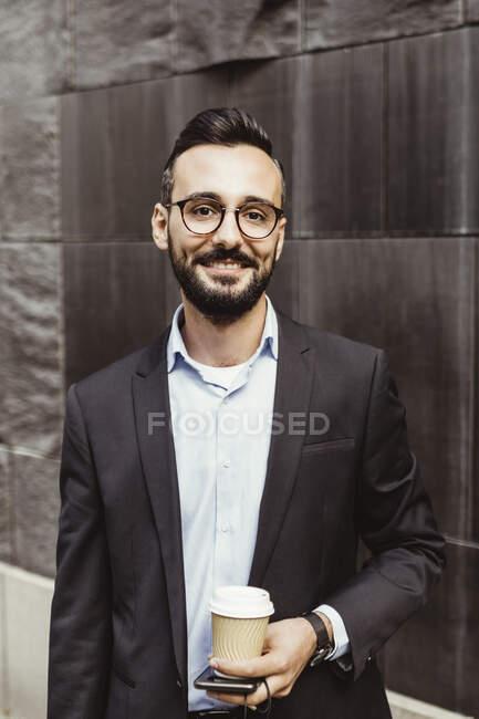 Portrait d'homme d'affaires confiant avec tasse jetable debout contre le mur — Photo de stock
