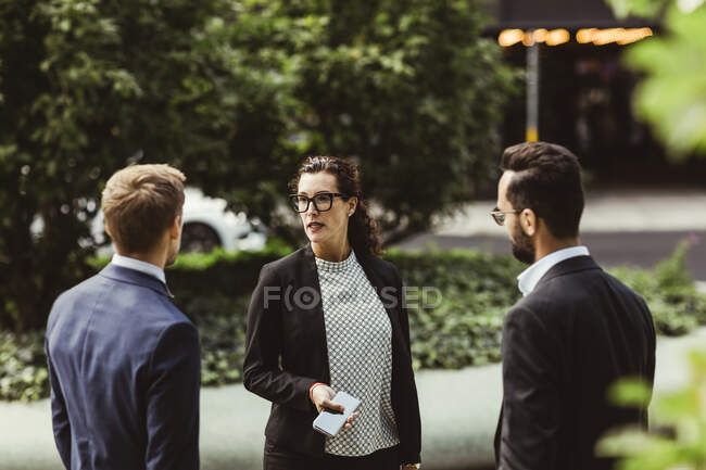 Male and female entrepreneurs discussing business strategy while standing outdoors — Stock Photo