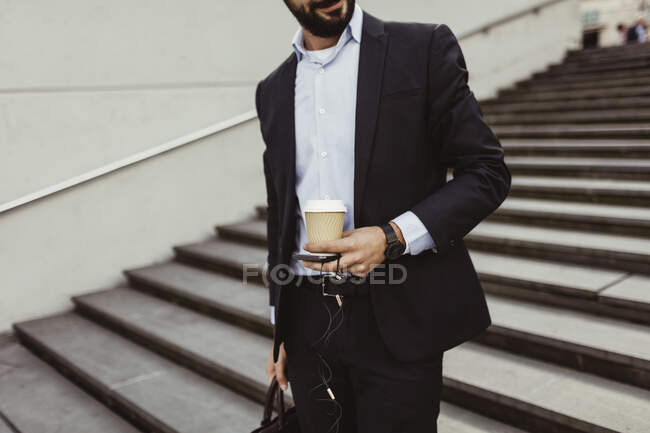 Midsection of business man with disposable cup and smart phone standing on staircase. - foto de stock