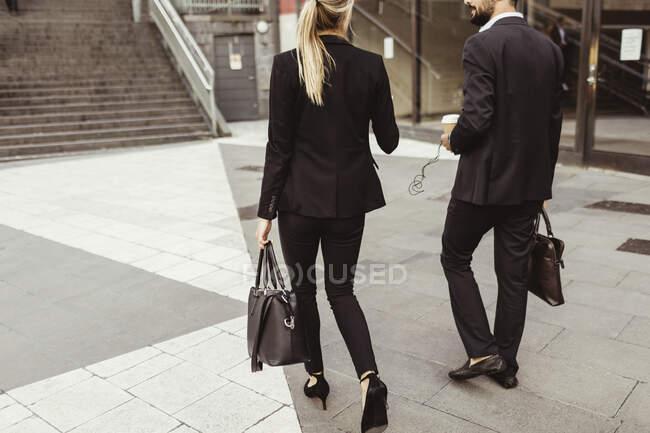 Vue arrière des gens d'affaires marchant et parlant à l'extérieur — Photo de stock