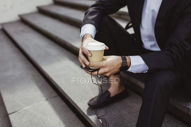Low section of businessman with disposable cup and smart phone sitting on staircase — Stock Photo