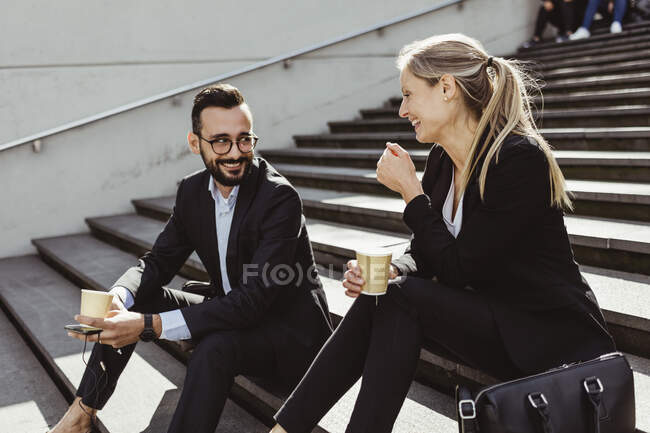 Smiling business people with coffee sitting on staircase - foto de stock