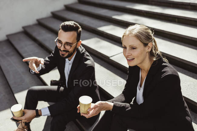 Smiling businessman pointing while sitting with female coworker on staircase — Stock Photo