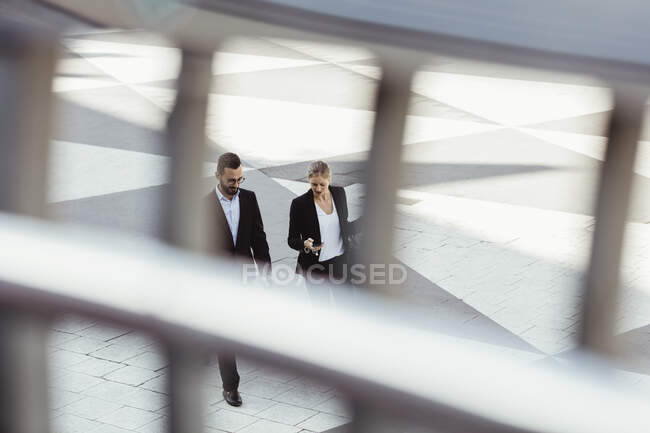 High angle view of male and female entrepreneurs talking while walking outdoors — Stock Photo