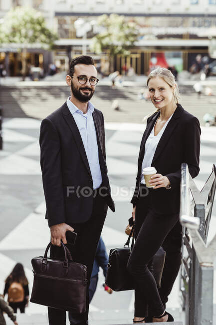 Portrait of smiling male and female professionals standing on staircase — Stock Photo