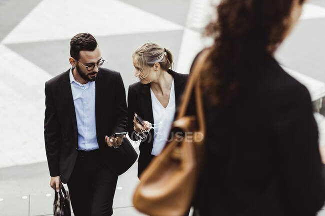 High angle view of female and male entrepreneurs talking while walking outdoors — Stock Photo