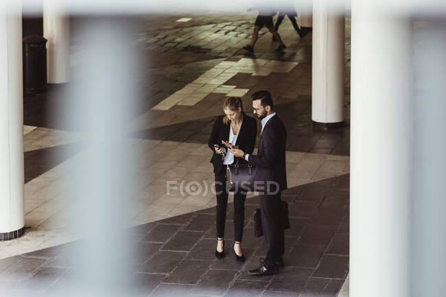 High angle view of business people using phone while standing on street — Stock Photo