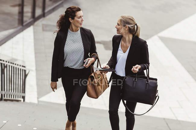 Empresária conversando com colega enquanto subia escada — Fotografia de Stock