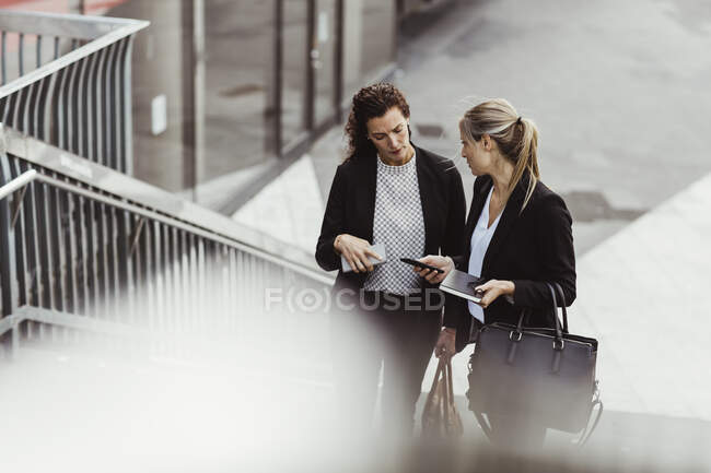Businesswoman showing smart phone to female colleague while discussing on steps — Stock Photo