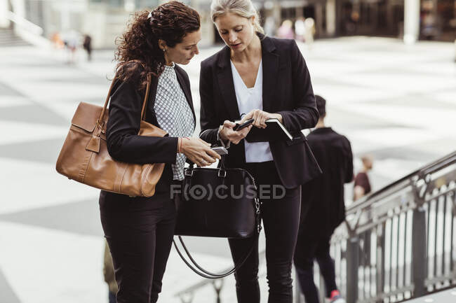 Businesswoman showing smart phone to female colleague while standing outdoors — Stock Photo