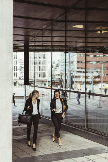 Businesswomen talking while walking on footpath — Stock Photo