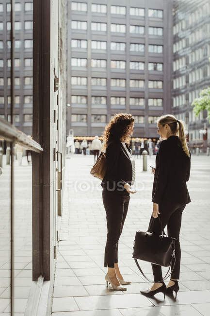 Businesswomen talking while standing by building — Stock Photo