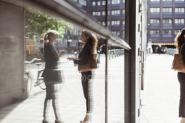 Reflection of businesswomen talking seen on building glass — Stock Photo