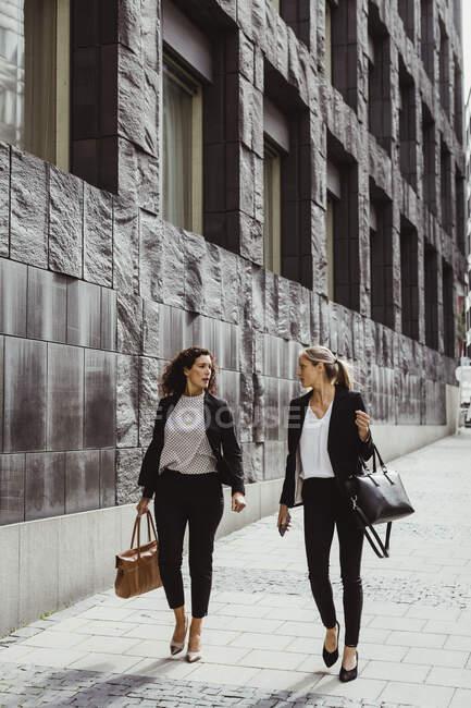 Предпринимательницы разговаривают во время прогулки по зданию — стоковое фото