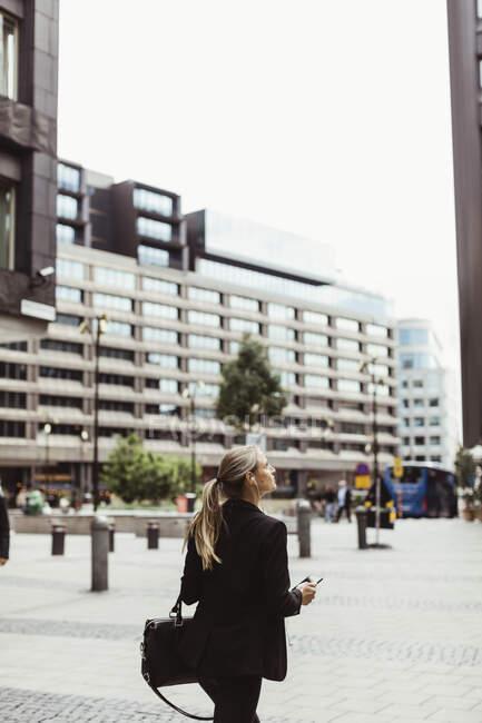 Femme entrepreneur levant les yeux tout en marchant à l'extérieur — Photo de stock