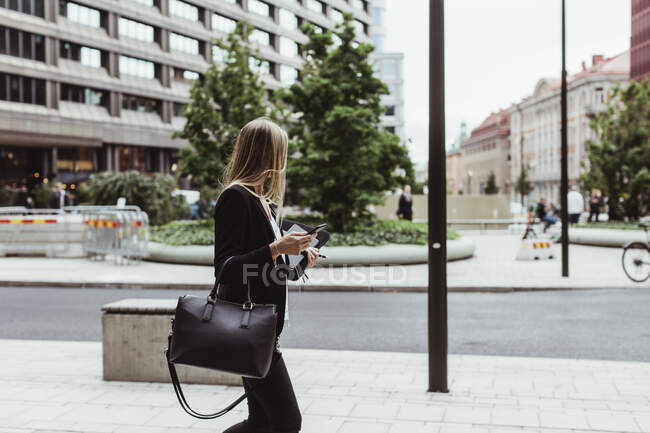 Side view of female entrepreneur with smart phone walking on sidewalk — Stock Photo