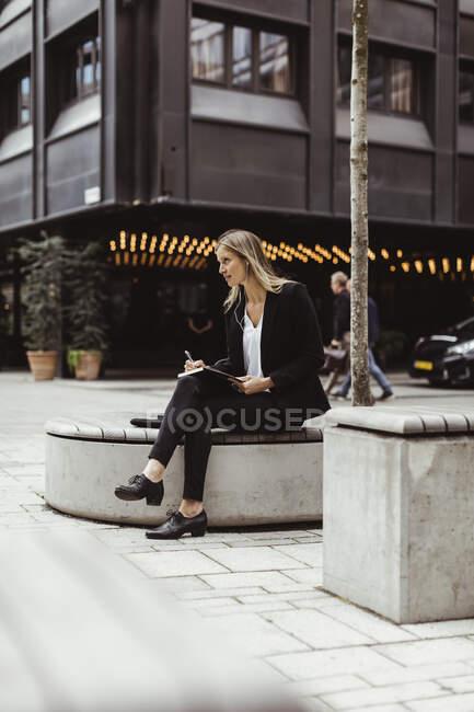 Femme d'affaires avec écouteurs intra-auriculaires regardant loin tout en étant assis à l'extérieur — Photo de stock