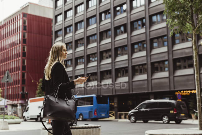 Female entrepreneur with smart phone walking against building — Stock Photo