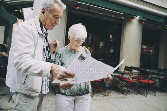 Senior coppia lettura mappa mentre in piedi sul marciapiede in città durante le vacanze — Foto stock
