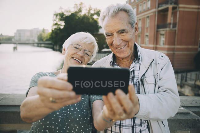 Sorridente coppia di anziani prendere selfie con il telefono cellulare mentre in piedi contro ringhiera in città — Foto stock