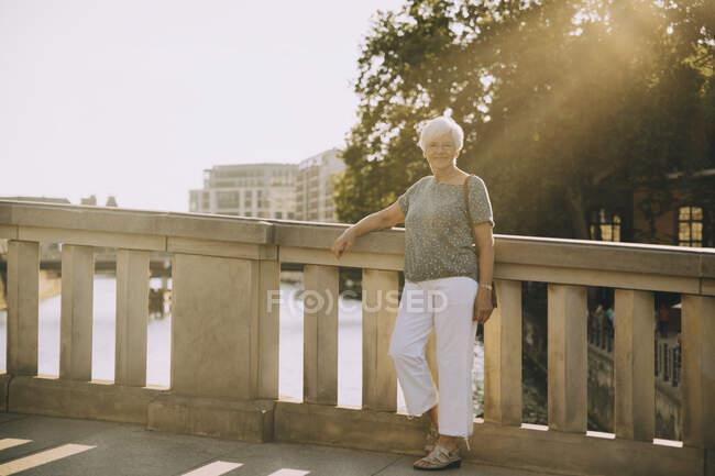 Ritratto a figura intera di donna anziana in piedi sul ponte contro ringhiera in città — Foto stock