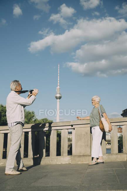 Larga duración de la toma de fotografías de mujeres mayores mientras se encuentran en un puente contra torre en la ciudad. - foto de stock