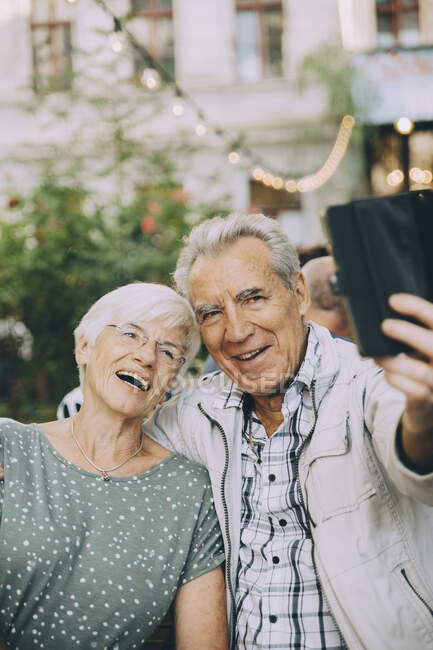 Senior man taking selfie with happy woman while sitting at restaurant in city — Stock Photo